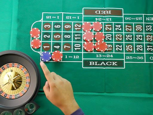 a girl standing in front of a roulette wheel