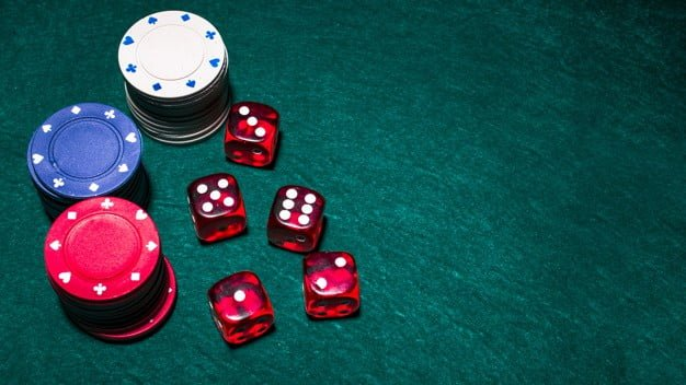 red dices and poker chips on a green table