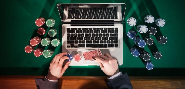 poker chips laying next to laptop