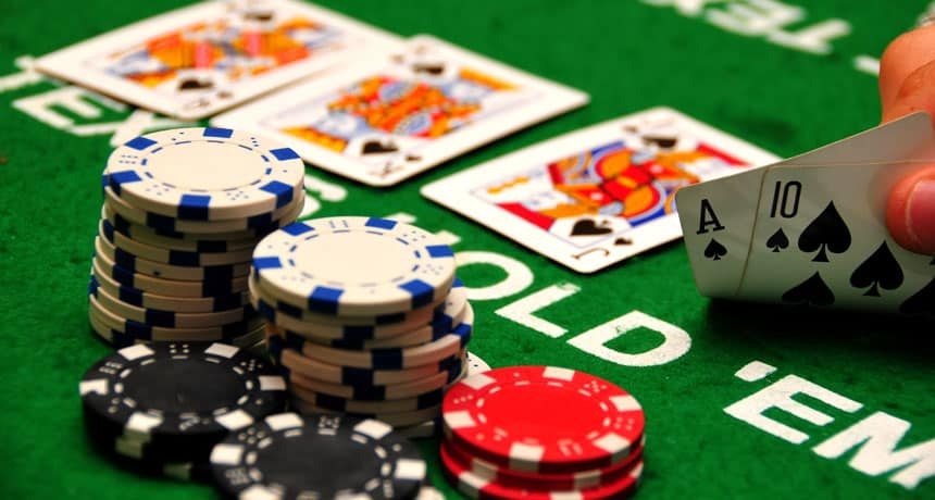 a hand holding ace and 10 next to a stack of poker chips