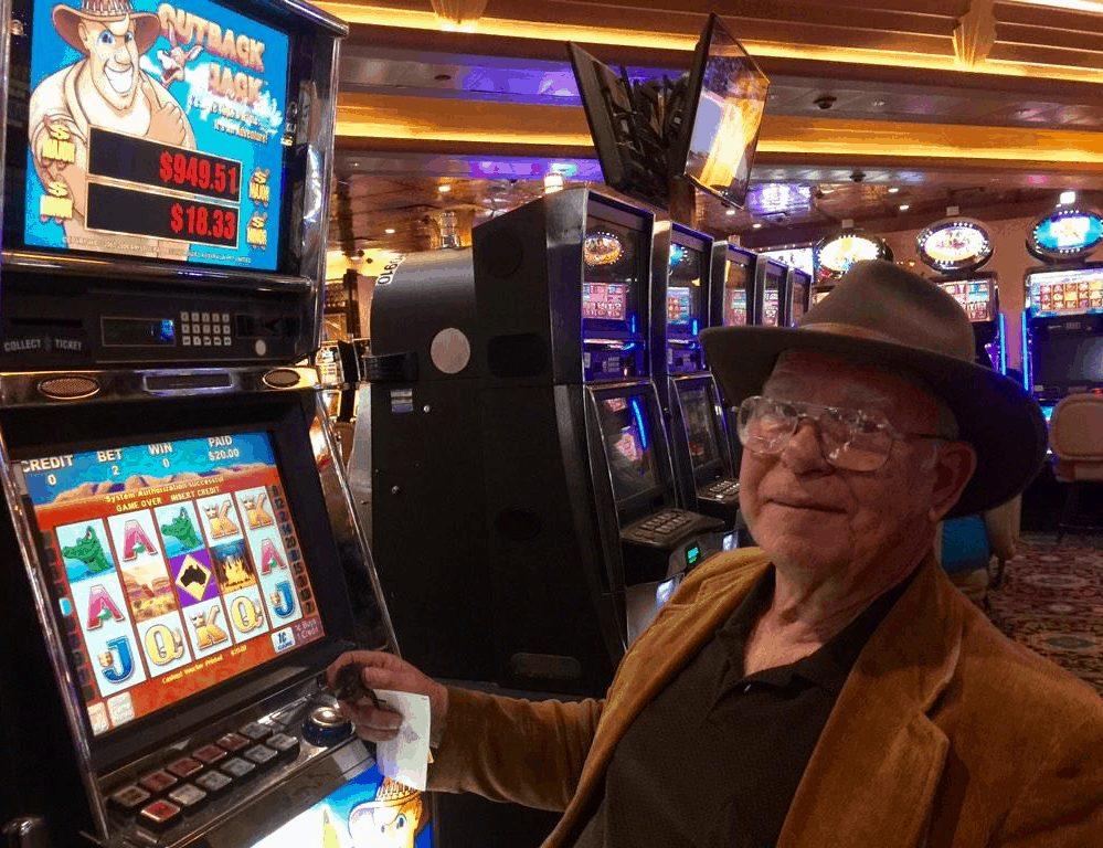an elderly man standing next to slot machines, smiling