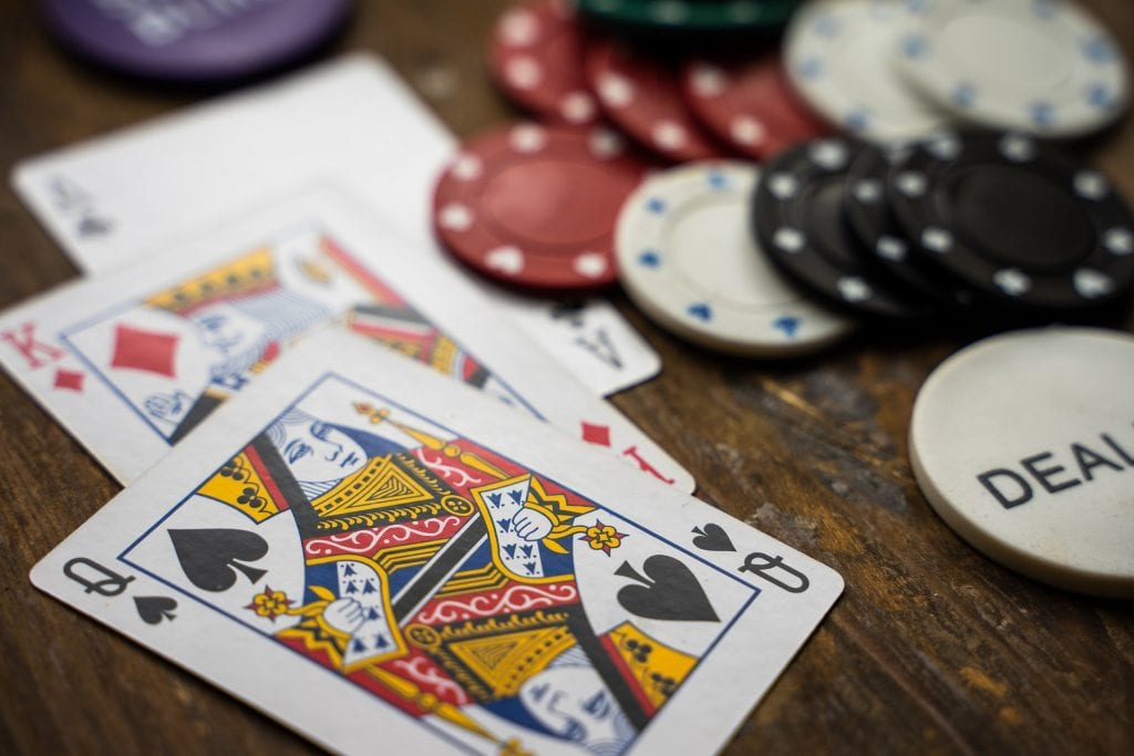 poker chips and cards on a wooden table